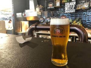 Gekühltes Korfu-Bier auf einem schwarzen Tresen einer griechischen Bar, im Flughafen Eleftherios Venizelos nahe Athen