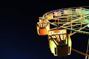 Gelb beleuchtetes Riesenrad von unten fotografiert