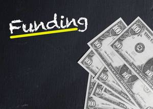 Gelb unterstrichenes Wort FUNDING (Finanzierung) mit Dollarnoten auf schwarzem Hintergrund