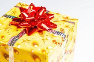 Gelb verpackte Geschenkbox mit roter Stern Schleife auf weißem Hintergrund