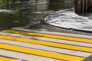 Gelb-weißer Zebrastreifen in Russland. Nasse Straße