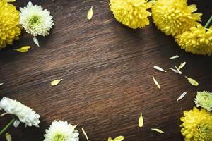 Gelbe Blumen formen einen Rahmen auf braunem Holztisch