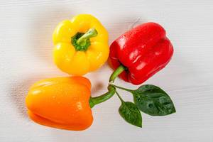 Gelbe, orange und rote Paprika, mit grünen Blättern, liegen auf einer weißen Oberfläche