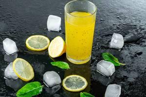 Gelber Cocktail im Glas mit Zitronenscheiben und Eiswürfel auf einem schwarzen Untergrund