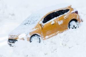Gelber Familienwagen auf einer verschneiten Straße