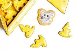 Gelber Lebkuchen in Form von Käse und einer Maus vor weißem Hintergrund Draufsicht