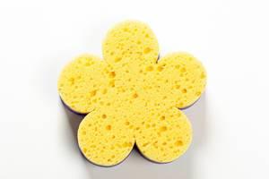 Gelber Putzschwamm in Form einer Blume vor weißem Hintergrund