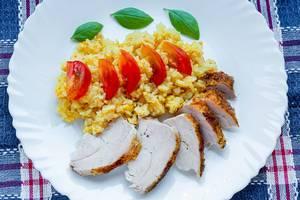Gelber Reis mit Hähnchenfleisch, Tomaten und Basilikumblätter auf einem weißen Teller und einem Tisch mit Tischdecke