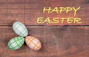 Gelber Text HAPPY EASTER (frohe Ostern) mit drei bemalten Ostereiern auf Holzhintergrund