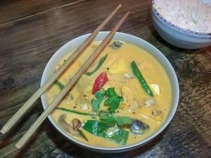 Gelbes Curry mit Pilzen, Paprika und Bohnen dekoriert mit Petersilie mit Reis Essstäbchen