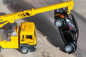 Gelbes Kranauto hebt ein schwarzes Spielzeugauto hoch, um es abschleppen zu können