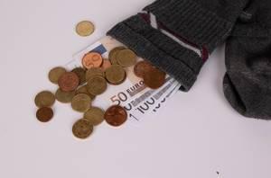 Geldscheine und Kleingeld stecken in einem alten Strumpf