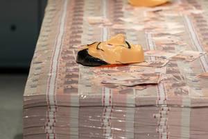 Geldstapel mit 50 Euro-Scheinen und der Salvador Dali Maske, bekannt von den Bankräubern aus Haus des Geldes von Netflix