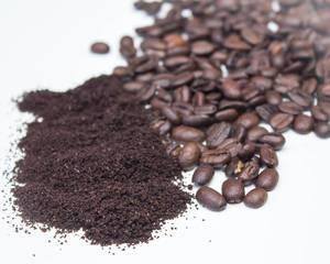 Gemahlener Kaffee neben gerösteten Kaffeebohnen auf weißem Tisch