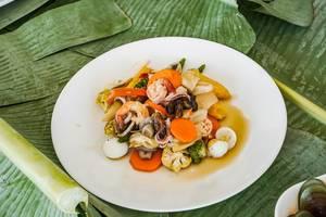 Gemischte Meeresfrüchte mit buntem Gemüse serviert in einem Teller auf Bananenblättern (Flip 2019)