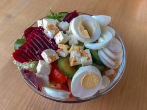 Gemischter Salat aus Ei, roter Bete, Fetakäse, Tomaten, Gurken und Karotten in Glasschale