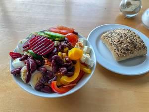 Gemischter Salat mit Bohnen, roter Bete, Paprika, gekochtem Ei, Tomaten, Käse und Vollkornbrötchen