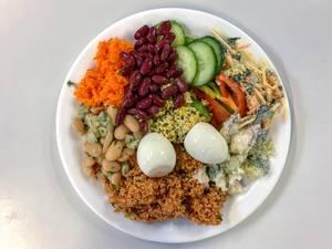 Gemischter Salat mit gekochtem Ei, Bohnen, Gurken, Karotten, Brokkoli und Couscous auf weißem Teller