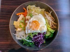 Gemischter Salat mit Tofu, Gurken, Sojasprossen, Karotten, Spiegelei und Sesam in Metallschüssel auf Holztisch
