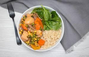 Gemüse-Curry aus Karotten, Kartoffeln, Erbsen uns Mais mit Reis und Baby-Spinat in einer Schüssel in der Aufsicht