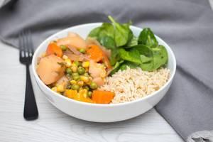 Gemüse-Curry aus Karotten, Kartoffeln, Erbsen uns Mais mit Reis und Baby-Spinat in einer Schüssel