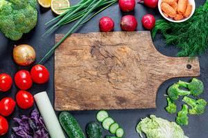 Gemüse und Greens formen einen Rahmen auf einem schwarzen Hintergrund und einem alten Küchenbrett in der Mitte
