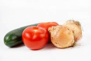 Gemüse und Kochzutaten wie Gurke, zwei reife Tomaten und ganze Zwiebeln auf einer weißen Oberfläche
