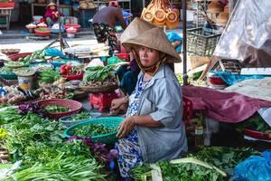 Gemüse-Verkäuferin mit geflochtenem Kegelhut auf einem Markt in Hoi Ann