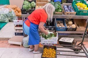 Gemüseverkäuferin mit Salat und Gemüse am Timeout Market in Lissabon