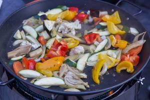Gemüsewok auf einer Gaskochplatte, mit Paprika, Zucchini, Blumenkohl und Aubergine