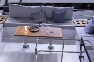 Gemütlich ausgestattetes Heck eines Bootes mit Tisch, Sitzbänken und Getränkehaltern