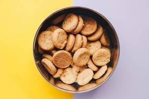 Geöffnete Dose Ingwer-Kekse auf gelben und lilanen Untergrund - Draufsicht in Nahaufnahme
