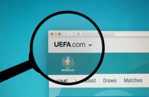 Geöffnete Internetseite auf Bildschirm mit Lupe über dem Logo der UEFA