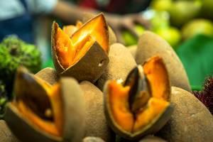 Geöffnete Zapote, eine tropische orange Frucht mit Kern und brauner Schale