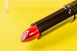 Geöffneter Lippenstift für knallrote Lippen isoliert vor gelbem Hintergrund
