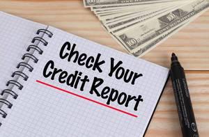 Geöffnetes Notebook mit rot unterstrichenem schwarzem Text Check Your Credit Report mit schwarzem Filzstift und Dollar Geldscheinen auf einem Holztisch