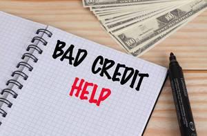 Geöffnetes Notebook mit schwarzem Text Bad Credit und rotem Text Help mit schwarzem Filzstift und Dollar Geldscheinen auf einem Holztisch