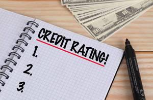 Geöffnetes Notebook mit schwarzem Text Credit Rating mit schwarzem Filzstift und Dollar Geldscheinen auf einem Holztisch