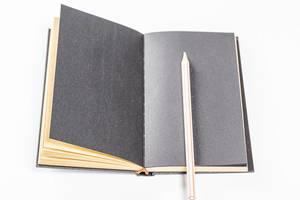 Geöffnetes Notizbuch mit schwarzen Seiten und einem weißen Stift