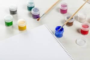 Geöffnetes Spiralheft mit bunten Farben und zwei Pinseln auf einem Holztisch