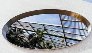 Geometrisches, ovales Loch in weißer Wand mit Blick auf Palmen und Dach aus Metallgitter