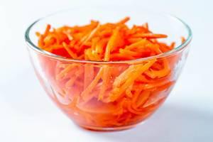 Geraffelte und marinierte Karotten in Glasschüssel vor weißem HIntergrund