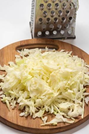 Geraffelter Kohl für Krautsalat auf Holzbrett neben Küchenreibe vor weißem Hintergrund