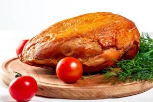 Geräucherte Hühnerbrust auf einem runden Holzbrett mit Dill- und Kirschtomaten