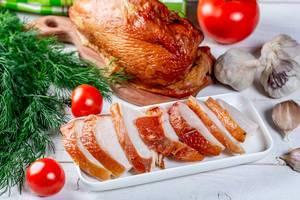 Geräuchertes Hähnchen mit Tomaten, Knoblauch und Kräuter auf weißem Tisch