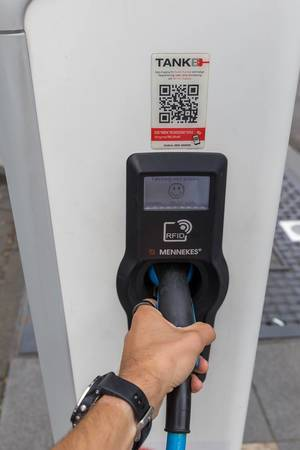 German TankE network for electric vehicles: men hand holds the plug in while his car is charging at a RheinEnerie station in Cologne