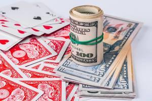 Gerollte Dollarnoten und Rommé-Spielkarten vor weißem Hintergrund