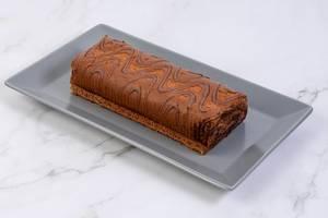 Gerollter Schokoladenkuchen mit Verzierung, auf einem grauen Tablett