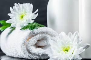 Gerolltes weißes Handtuch dekoriert mit Chrysanthemeblüten vor Kosmetikflaschen