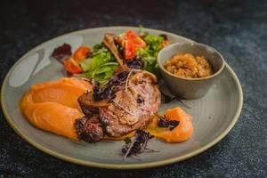 Geröstete Entenbrust mit Kürbispüree und einem frischen Salat - Nahaufnahme